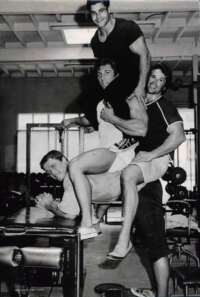 Arnold-Schwarzenegger-doing-donkey-calf-raises-with-three-friends-on-his-back