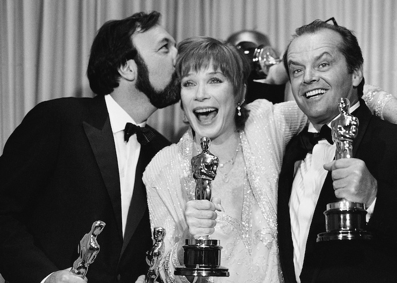 "Director James Brooks, left, gives actress Shirley MacLaine a congratulatory kiss as Jack Nicholson stands by after winning Oscars for their participation in the film, ""Terms of Endearment"" during Academy Awards ceremony in Los Angeles on Monday, April 10, 1984. (AP Photo)"