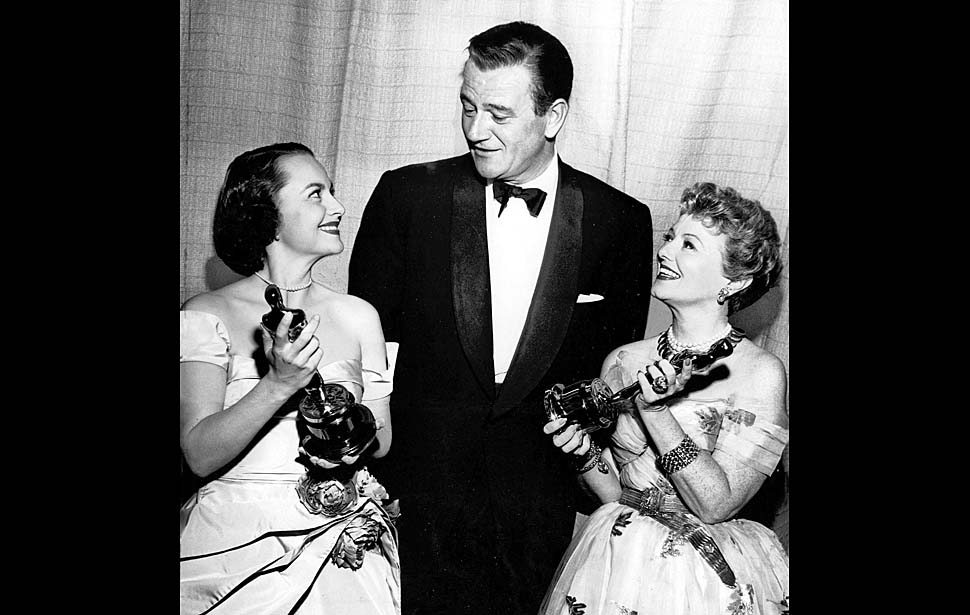 John Wayne is shown with Olivia de Haviland, left, and Janet Gaynor as he accepted Oscars for Gary Cooper and John Ford, who were unable to attend. (Los Angeles Times Photo)