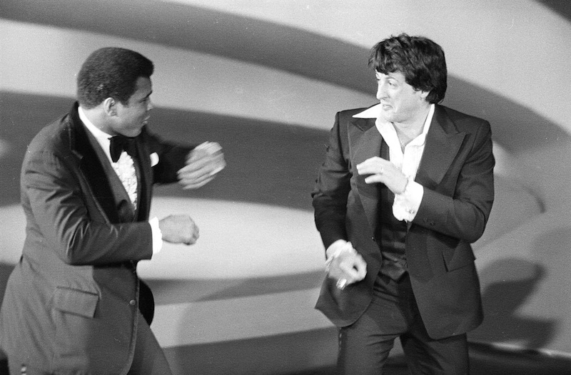 "Heavyweight champion Muhammad Ali, left, makes a suprise appearance on the Academy Awards show, staging a sparring with Sylvester Stallone, actor and screenwriter of the boxing drama ""Rocky,"" on March 28, 1977, in Los Angeles, California. (AP Photo)"