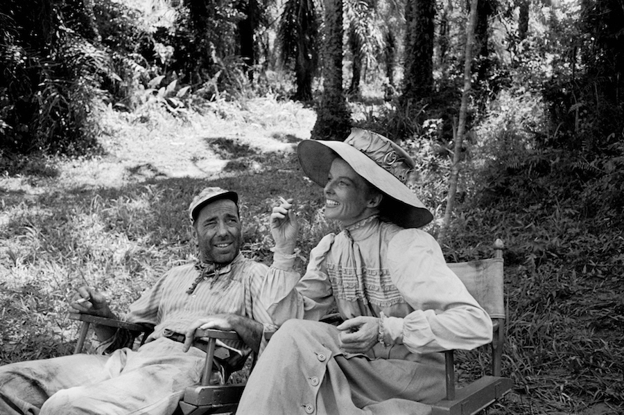 "(L-R) Actors Humphrey Bogart and Katharine Hepburn relaxing during location shooting on ""The African Queen."""